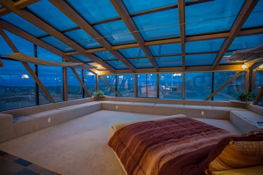 This angle of the bedroom shows you the gorgeous view of the glass wall and glass ceiling that covers most of the bedroom paired with built-in seats lining the walls for a unique reading area. Images courtesy of Toptenrealestatedeals.com.