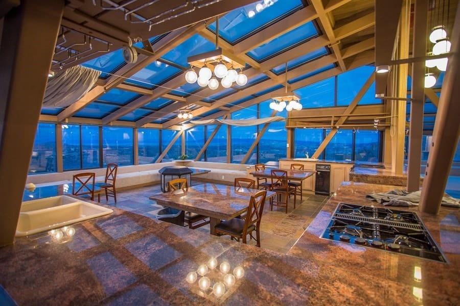 This gorgeous open area houses the kitchen and dining area in one large space. You can see here that the kitchen is placed at the edges with earthy countertops to match the flooring while the dining sets are on the open floor space in the middle under the glass ceiling. Images courtesy of Toptenrealestatedeals.com.