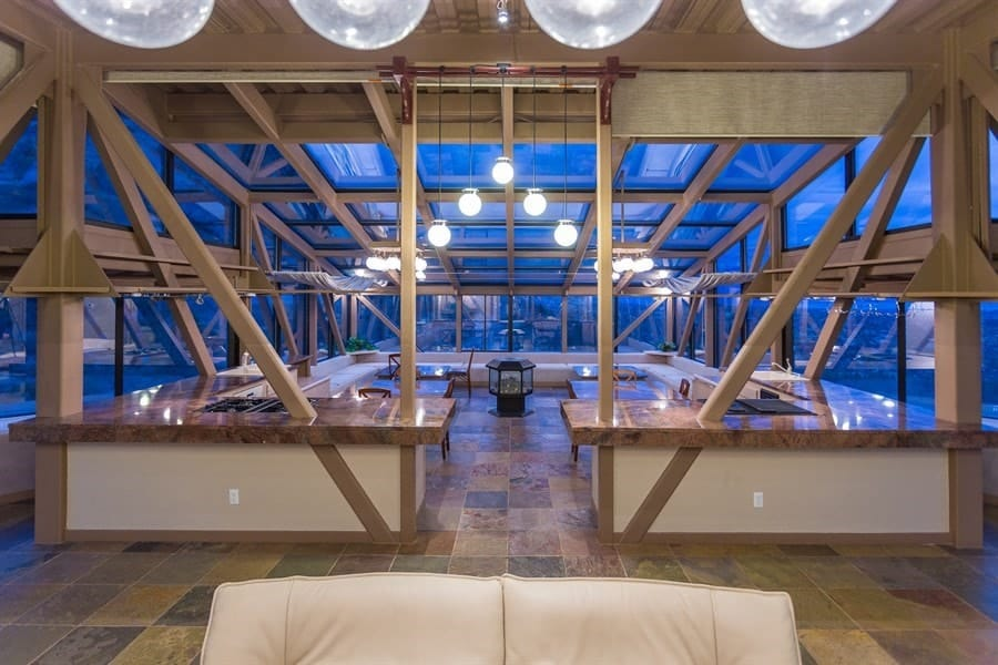 This is the entrance to the kitchen and dining area through a space in between the kitchen countertops and beams. The combination of the warm modern lighting, glass walls and glass ceiling create a unique aesthetic that is simple breathtaking. Images courtesy of Toptenrealestatedeals.com.