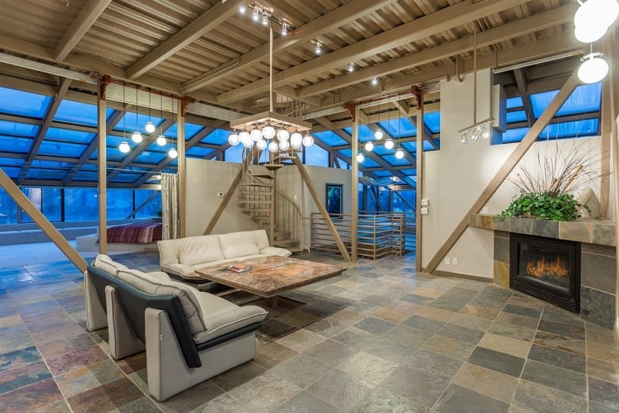 This is a simple yet cozy living room with a couple of gray cushioned sofas facing a square wooden coffee table topped by a decorative chandelier hanging from the ceiling with exposed beams and modern lighting. Images courtesy of Toptenrealestatedeals.com.
