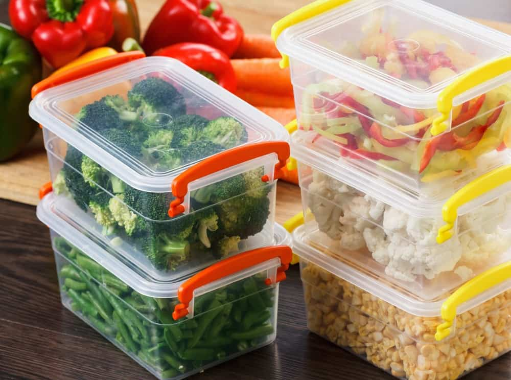 Stacked storage of raw veggies in plastic containers.