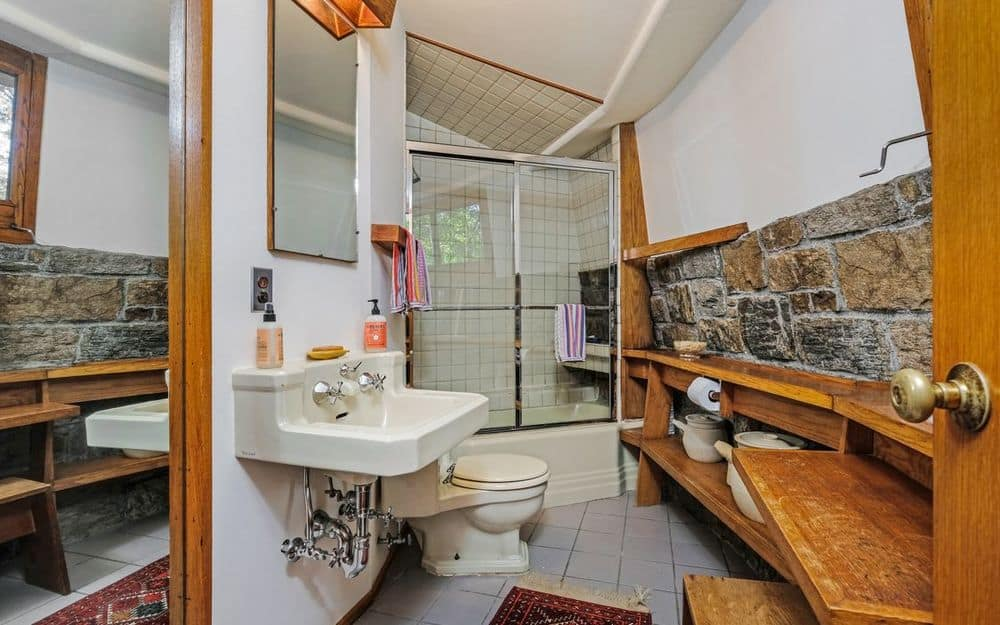 This is a charming intimate bathroom with a floating sink across from the built-in wooden shelving leading to the glass-enclosed shower area on the far side. Images courtesy of Toptenrealestatedeals.com.