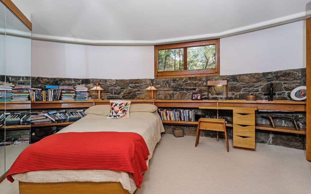 This spacious room has a bed that is attached to a large wooden structure serving as headboard as well as bedside table and has a built-in desk at the edge. Images courtesy of Toptenrealestatedeals.com.