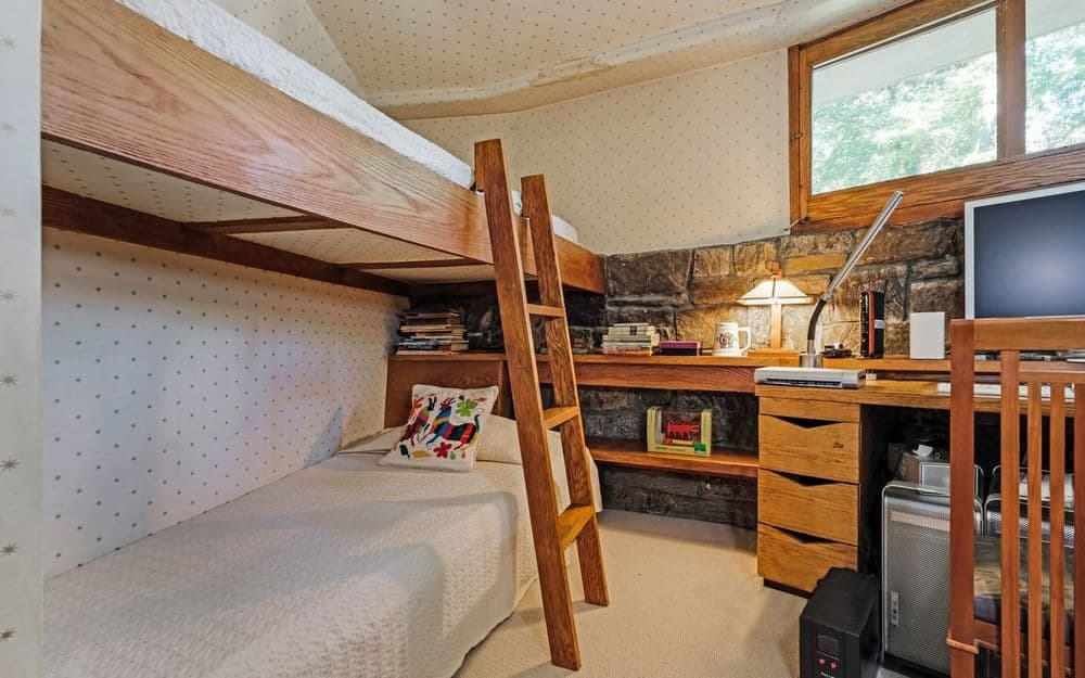 This bedroom has a large wooden structure built into the stone wall that houses two beds as well as a built-in desk and dresser on the side. Images courtesy of Toptenrealestatedeals.com.