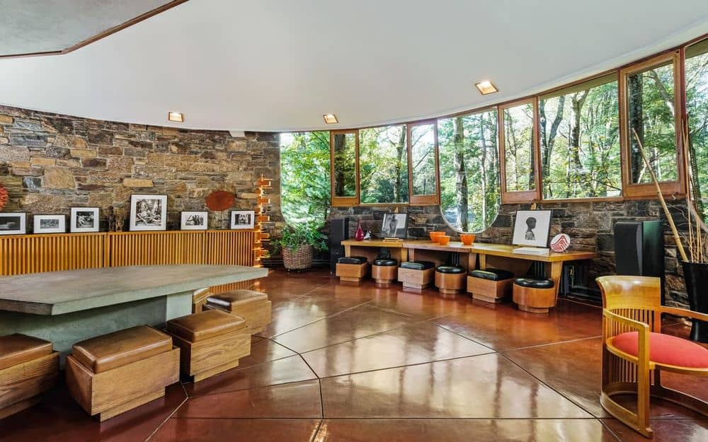 Beyond the game table is a lovely long wooden table that is built into the stone wall topped with tall glass walls that give a nice view of the trees outside. Images courtesy of Toptenrealestatedeals.com.