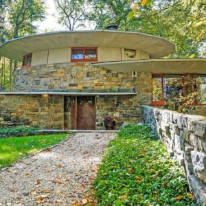 This is the charming home designed to look like a mushroom that grew naturally from the ground. It has earthy stone exterior walls that pair well with the graveled walkway flanked by grass lawns. Images courtesy of Toptenrealestatedeals.com.
