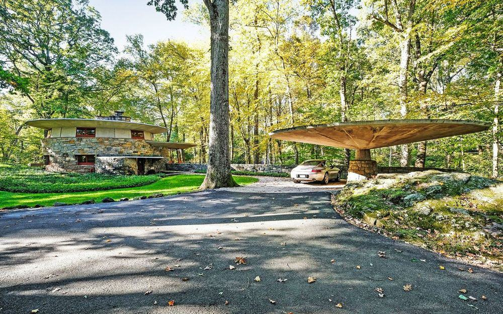 This is a view of the house and its carport from the vantage of the driveway. This view lets you appreciate the lush green landscape surrounding the property filled with tall trees and grass. Images courtesy of Toptenrealestatedeals.com.