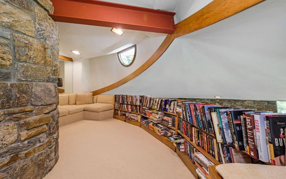 This is the charming library with a long row of bookshelves following the lay of the curved wall leading to the far end that has a comfortable L-shaped sofa for a reading nook. Images courtesy of Toptenrealestatedeals.com.