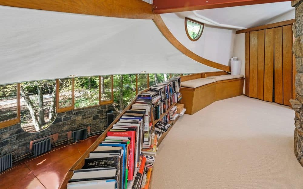 This is the other side of the lovely library on the other side of the long curved row of bookshelves is a cushioned bench by the window for a nice reading nook. Images courtesy of Toptenrealestatedeals.com.