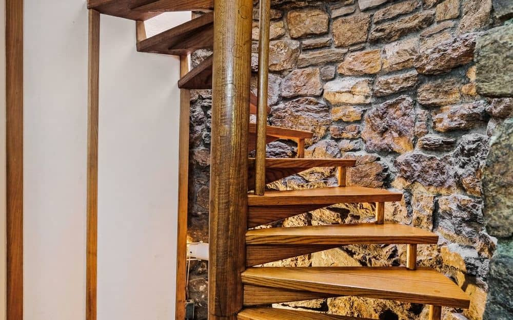 This is a closer look at the spiral stairs that has wooden steps supported by a thick pillar and has a background of a charming stone wall. Images courtesy of Toptenrealestatedeals.com.