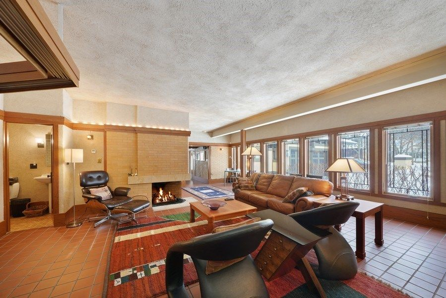 A family living room offering an elegant brown leather couch and two modish chairs along with a fireplace in the corner. Images courtesy of Toptenrealestatedeals.com.