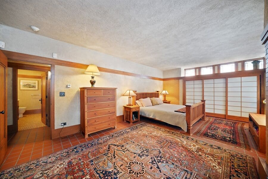 Large bedroom suite with a large classy bed set and a large area rug, along with a personal bathroom. Images courtesy of Toptenrealestatedeals.com.