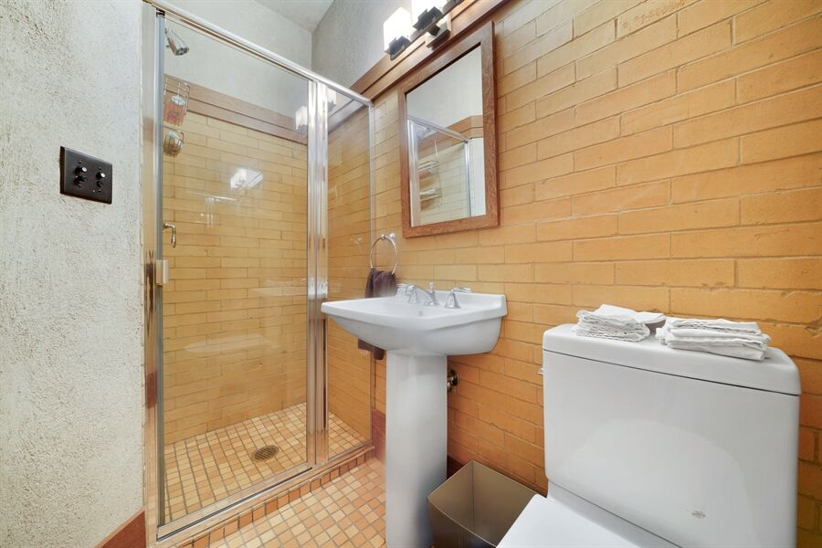 A bathroom with a walk-in shower and a pedestal sink, along with a toilet on the side. Images courtesy of Toptenrealestatedeals.com.