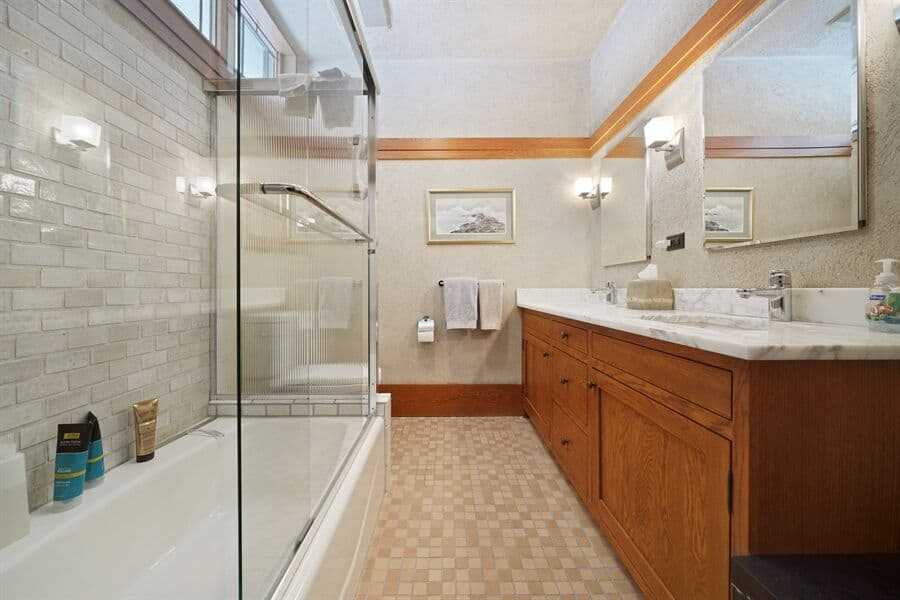 This bathroom offers a bathtub and shower combo, along with a sink featuring a marble counter. Images courtesy of Toptenrealestatedeals.com.