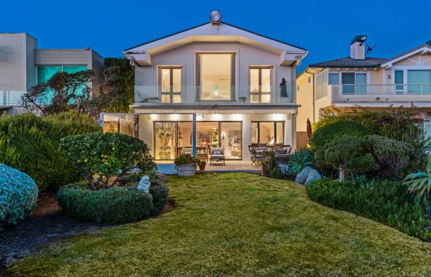 This is a view of the cozy and homey house with beige walls complemented by the brilliant yellow lights coming from the large windows of the two levels. These pair perfectly well with the lush and vibrant green landscaping of the backyard. Images courtesy of Toptenrealestatedeals.com.