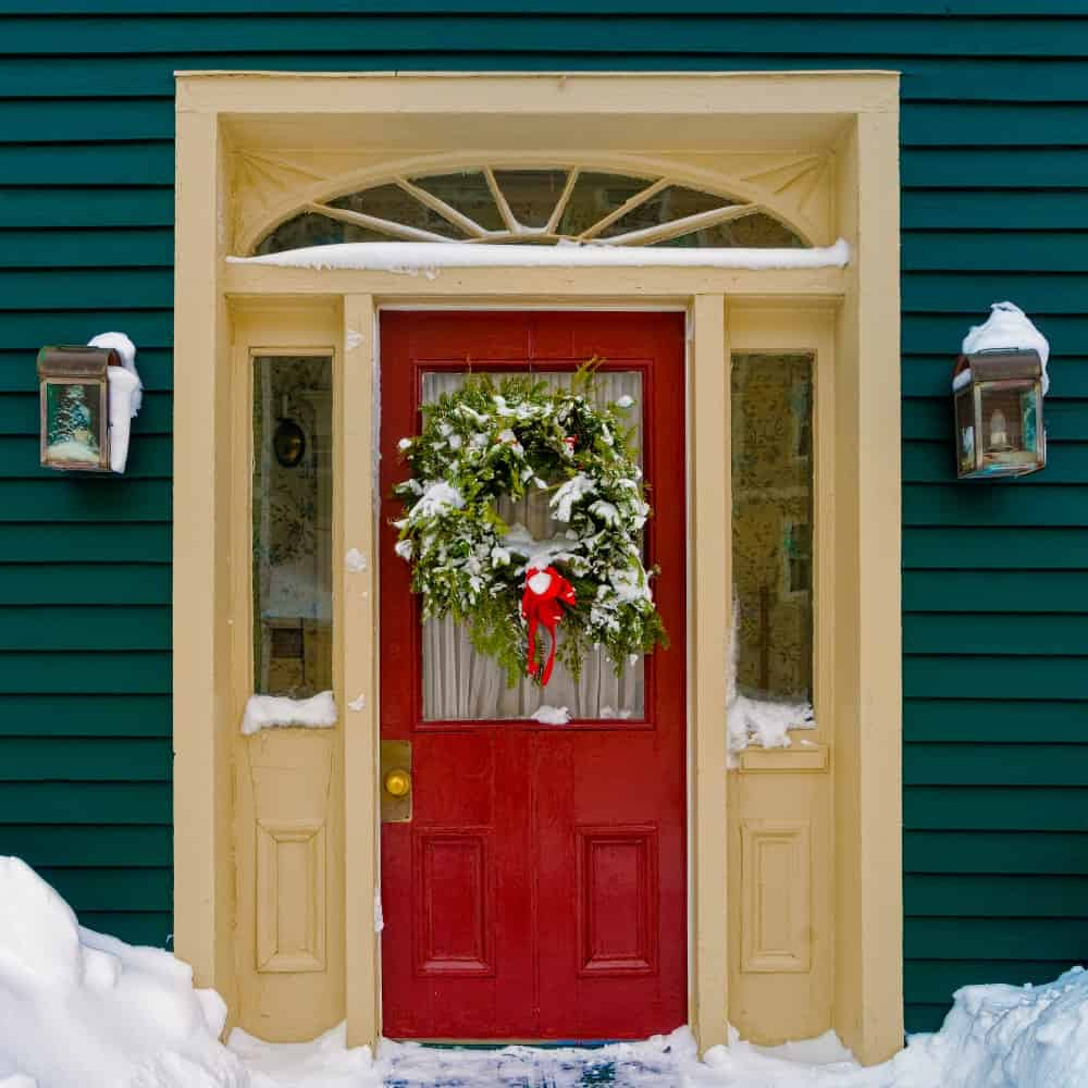 House with a green exterior siding, wall sconces, and a red front door decorated with a Christmas wreath and partly covered in snow.