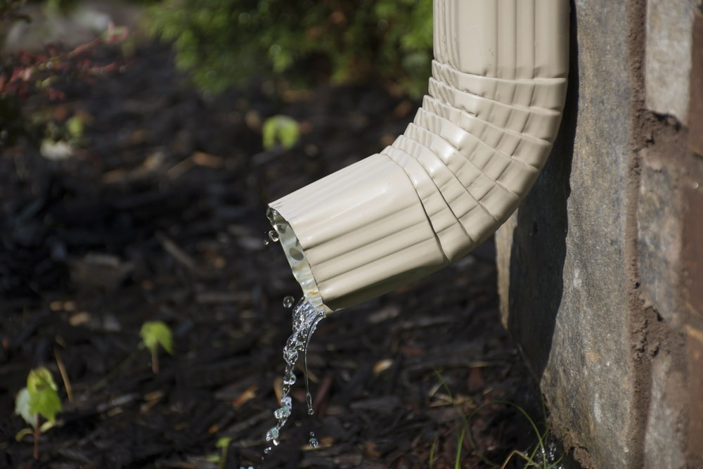 A close look at the down spout of the aluminum rain gutter of the house.