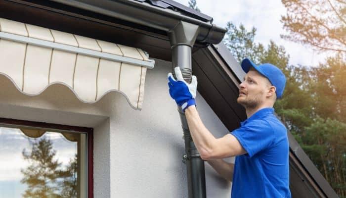Gutter contractor installing downspurt