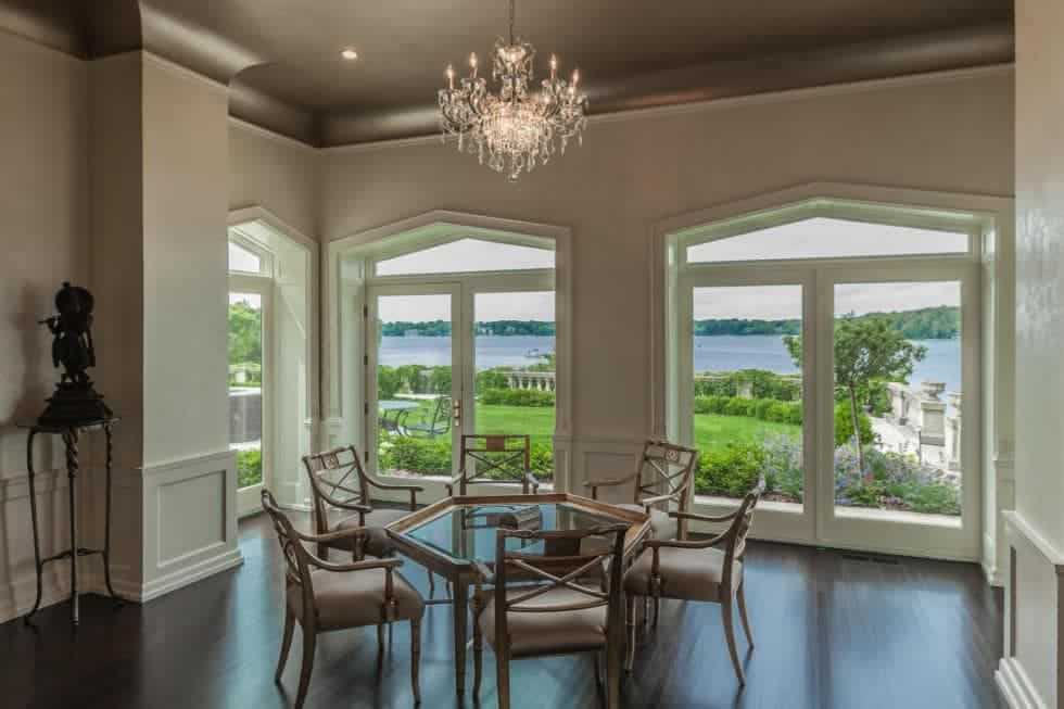This large and airy formal dining room has the same dark hardwood flooring that balances the bright beige walls with arched windows and gray tray ceiling that hangs a crystal chandelier over the geometric glass-top table. Images courtesy of Toptenrealestatedeals.com.