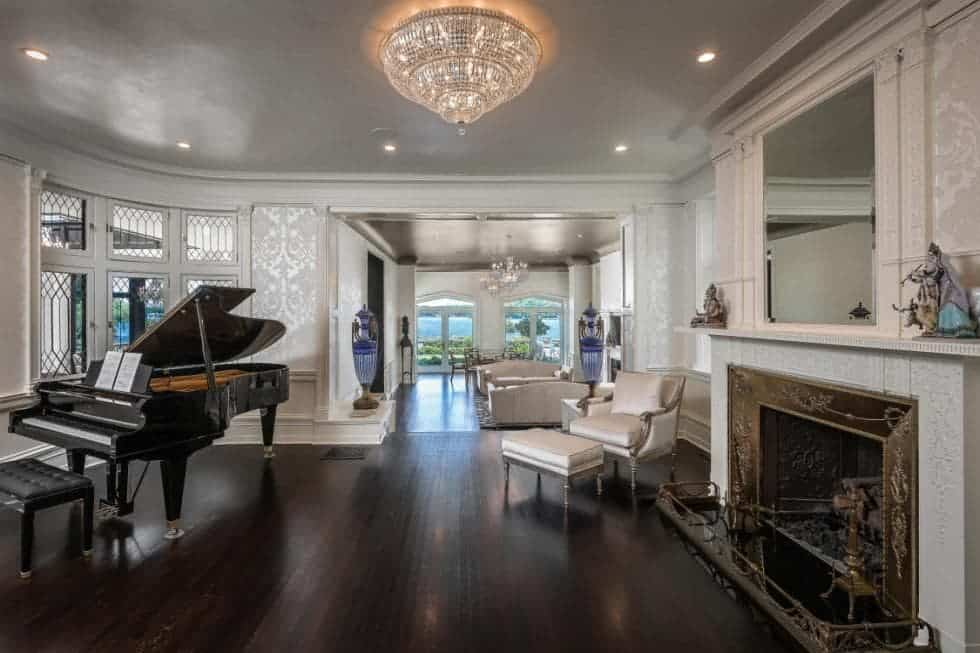 This is a large great room that houses a living room on the far side and a grand piano next to the large fireplace with a white mantle that stands out against the wide luxurious dark hardwood flooring topped with a crystal flush-mount lighting. Images courtesy of Toptenrealestatedeals.com.