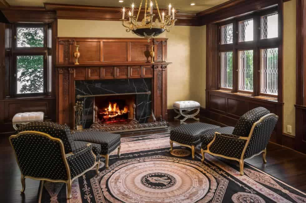 This is a charming and homey living room with a couple of comfortable cushioned arm chairs with matching foor stools facing a large fireplace with elegant wooden mantle that matches the moldings of the room. Images courtesy of Toptenrealestatedeals.com.