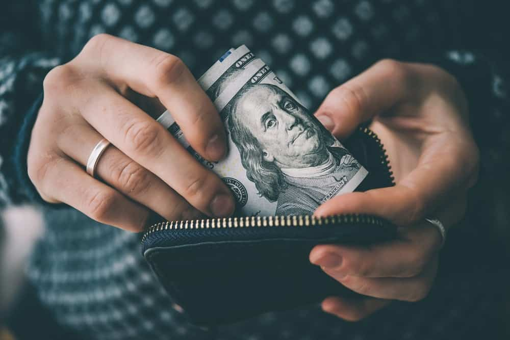 Close-up of hands holding folded dollar bills and an open money pouch.