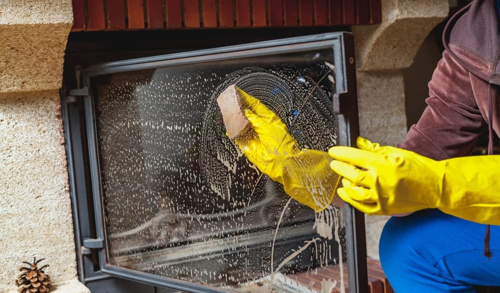 A pair of gloved hands cleaning the fireplace glass with soapy water.