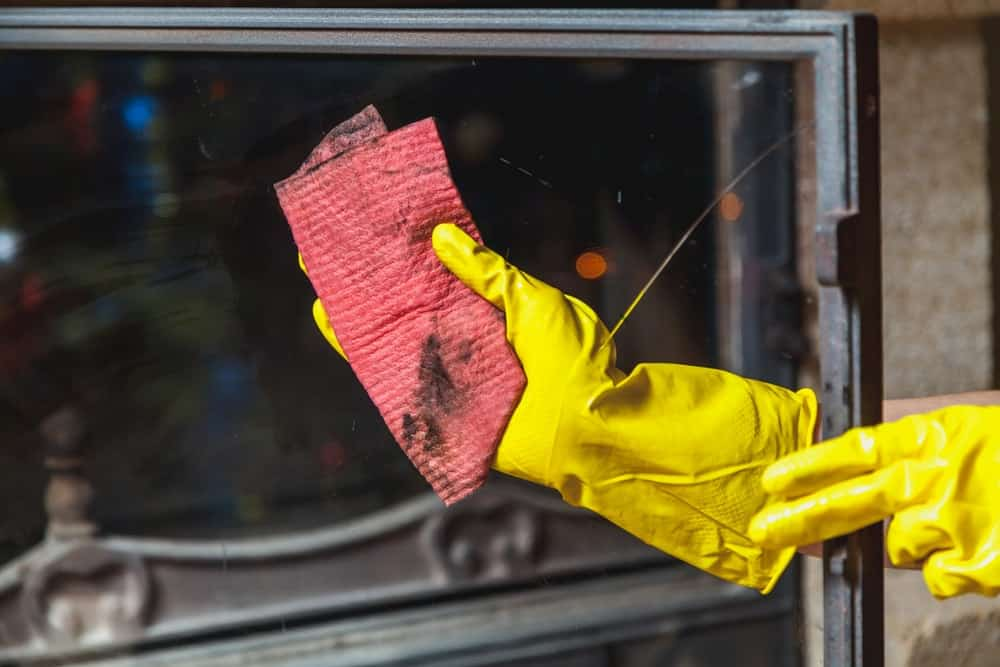A gloved hand wiping the clean and clear fireplace glass using a rag.