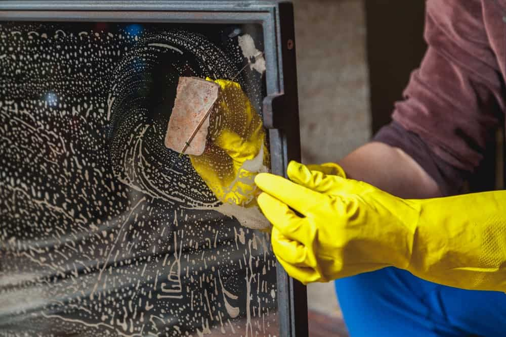 A pair of hands washing and cleaning the soot off the fireplace glass.