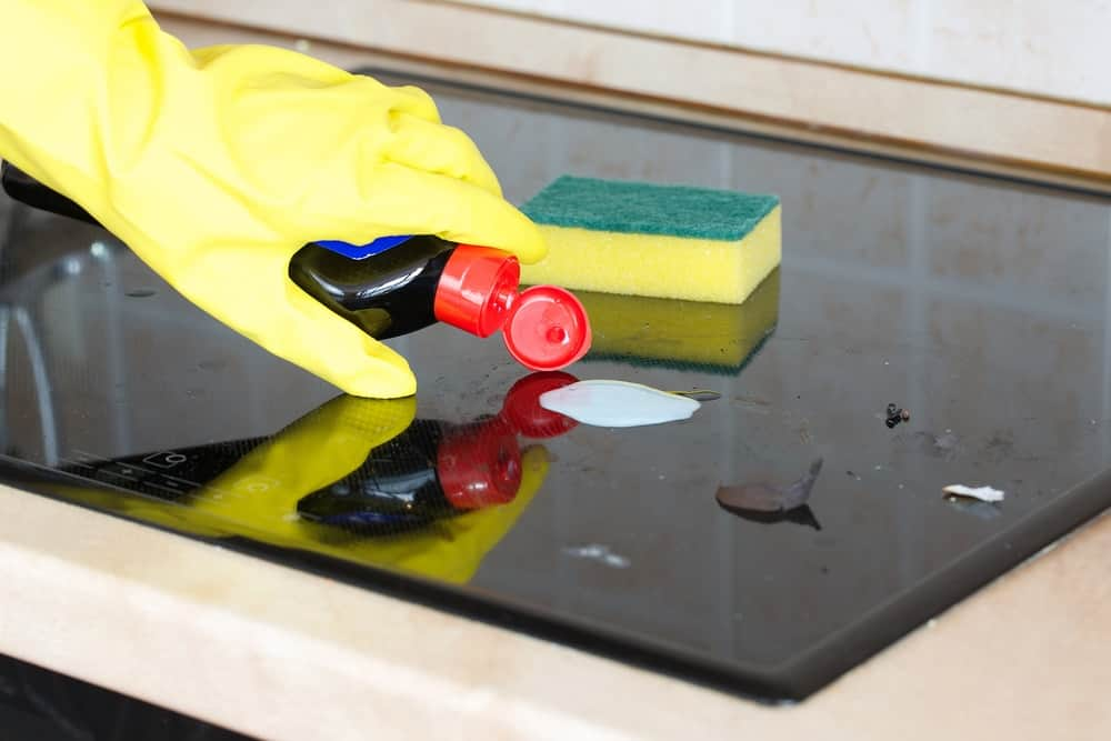 A gloved hand applying cleaner on a glass stove top.