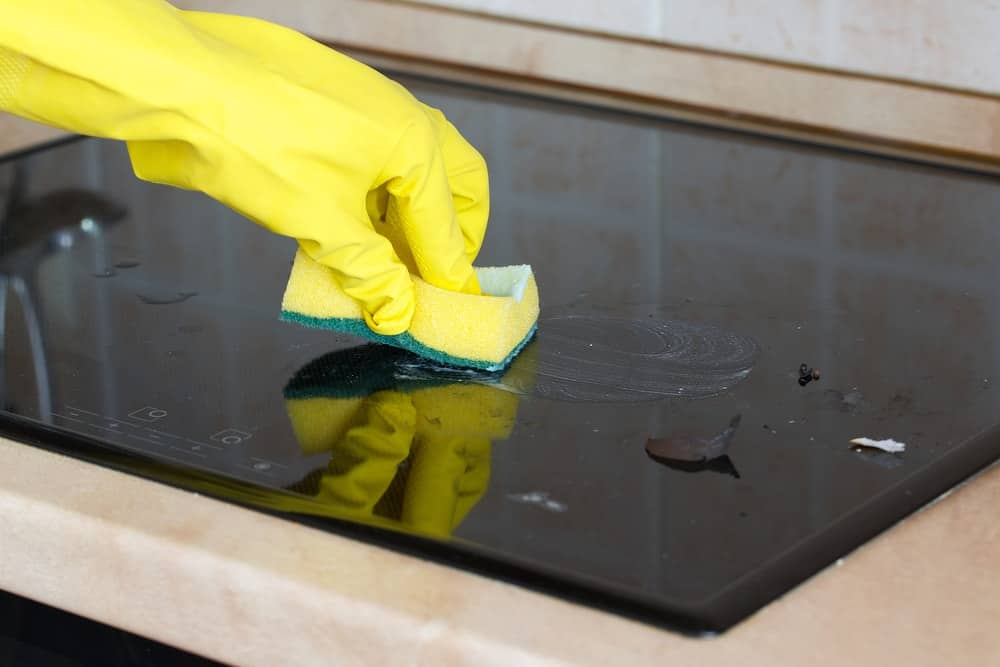 A gloved hand cleaning the glass stove top using a sponge.