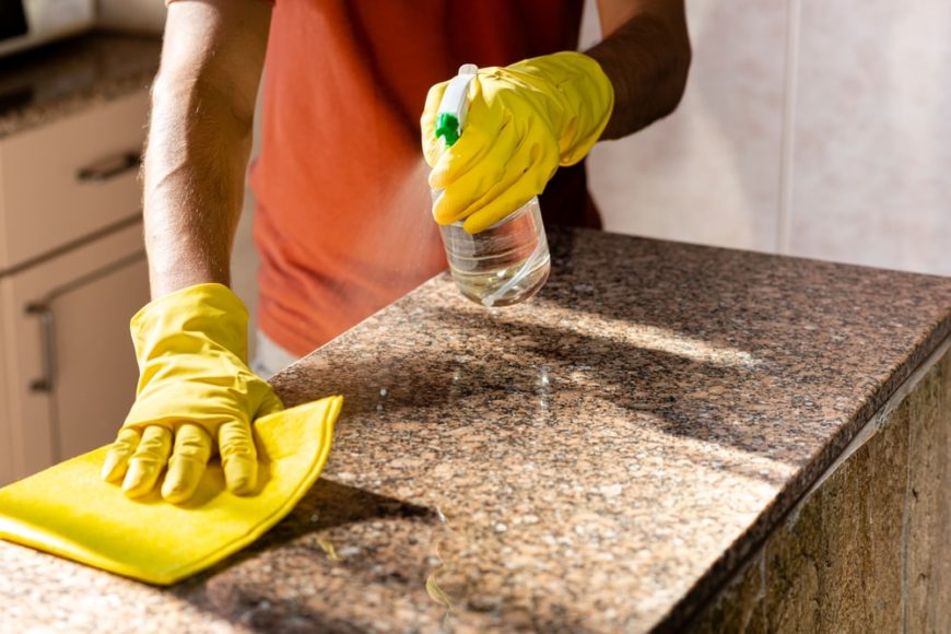 A man cleaning the granite countertop in the kitchen.