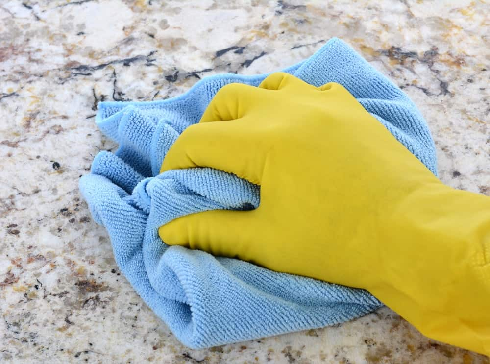 A gloved hand wiping the granite countertop using a fabric.
