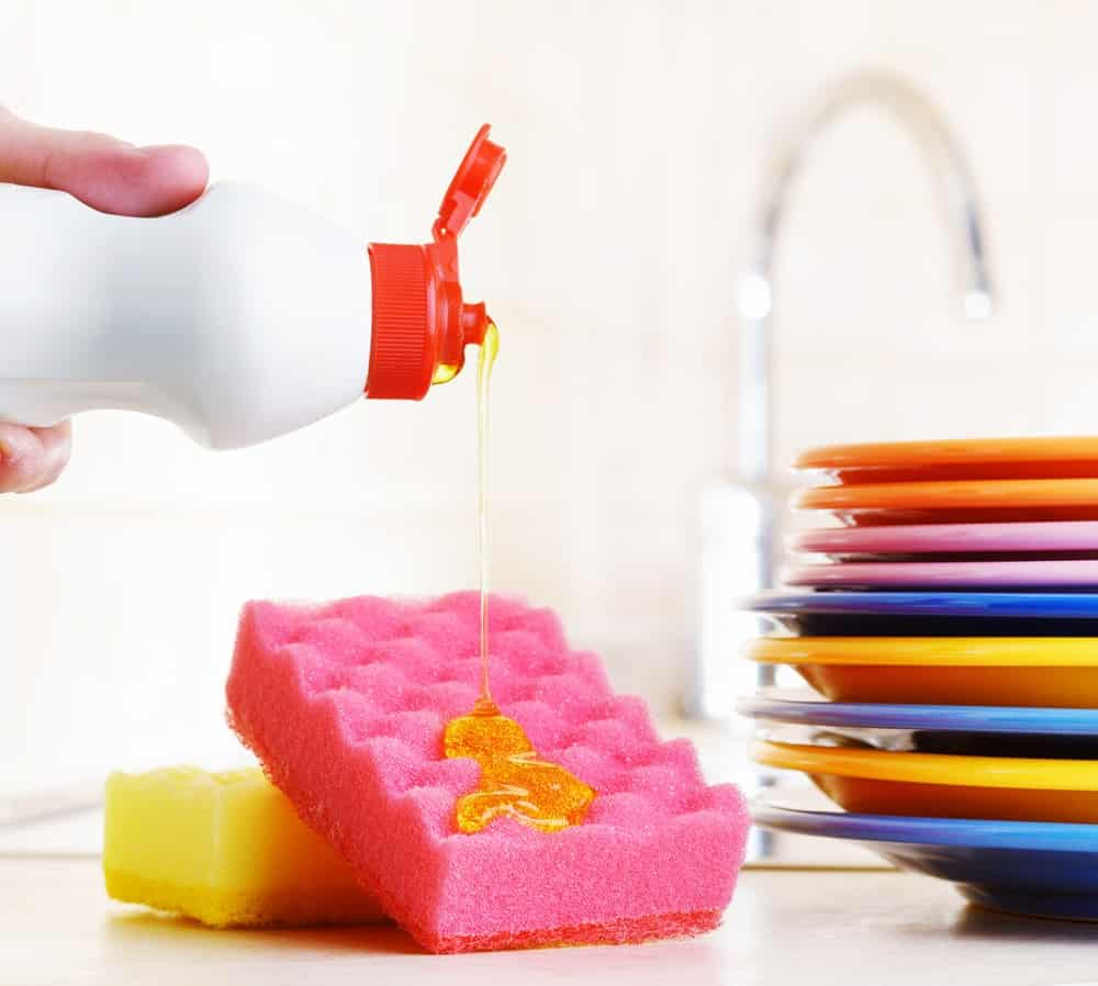A hand pouring liquid dish soap on a sponge.