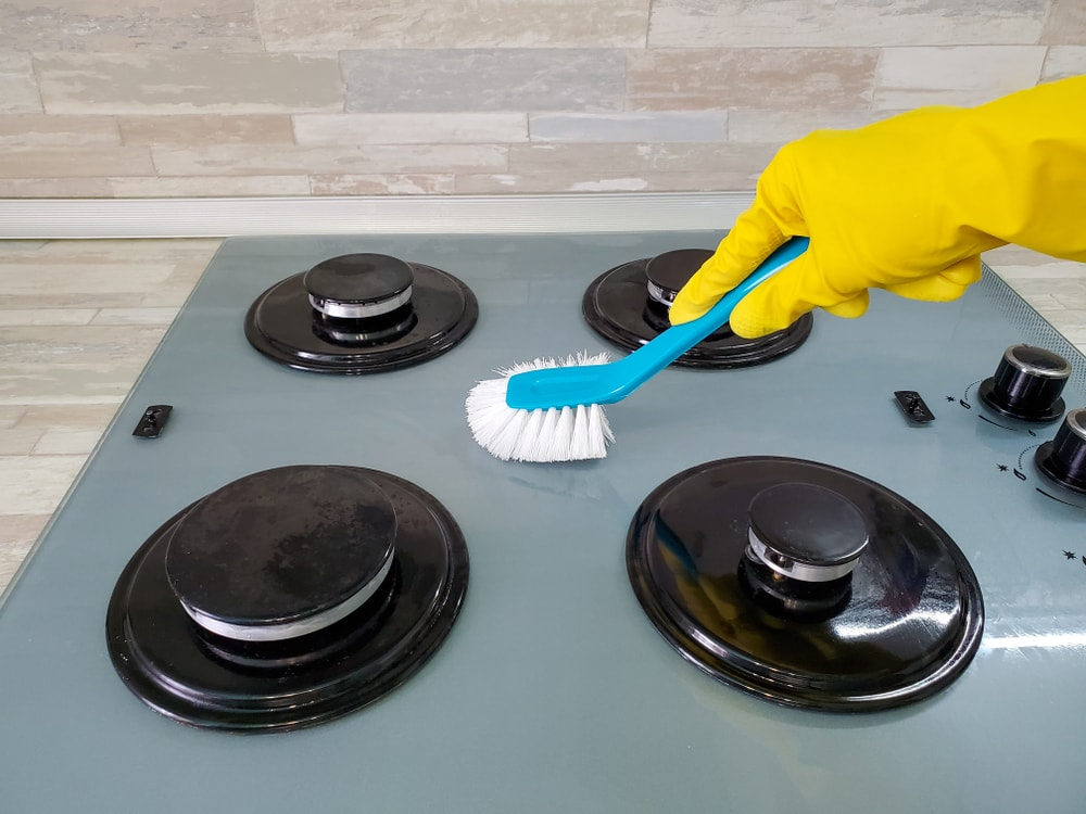 A gloved hand scrubbing the stove top.