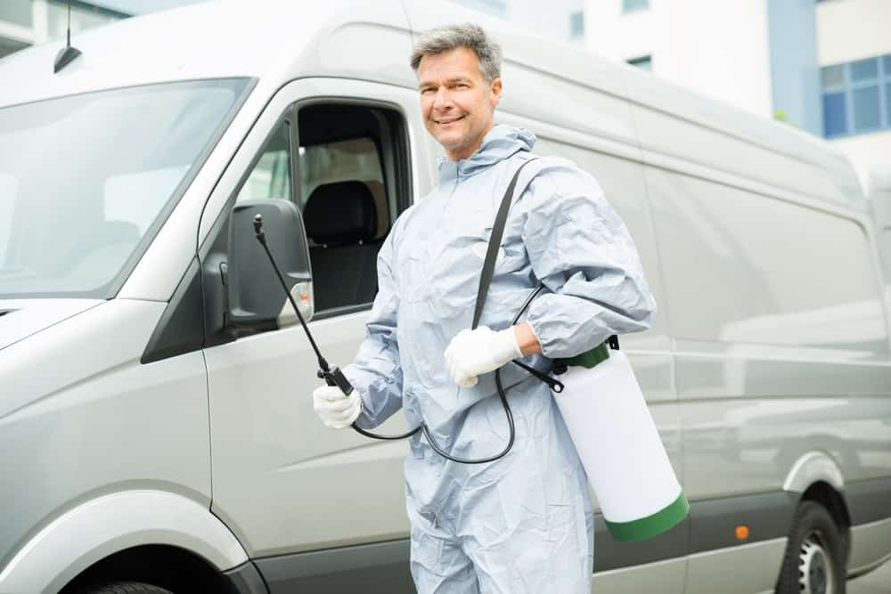 An exterminator with insecticide sprayer.