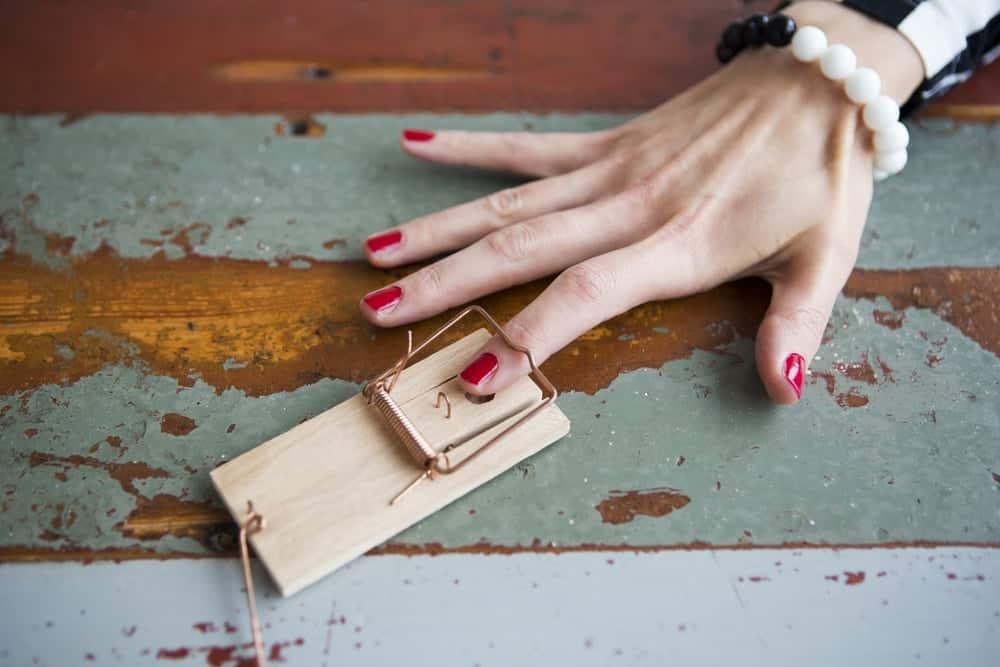 A woman's finger caught in a small mouse trap.