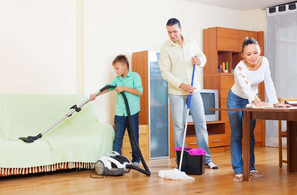 A family helping each other clean the house.