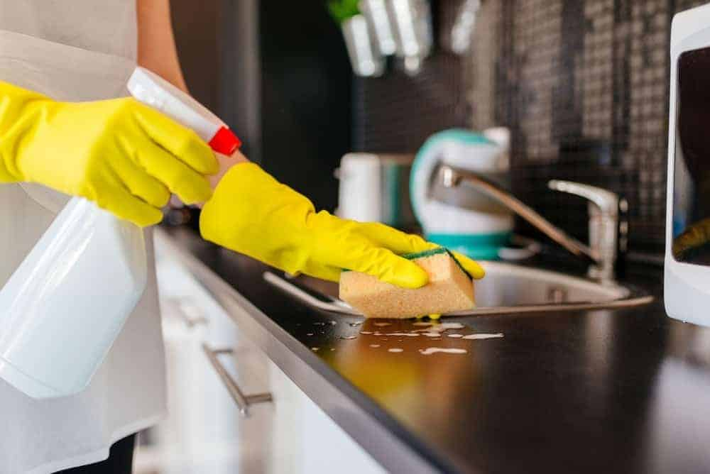A woman with yellow gloves cleaning the kitchen counter.