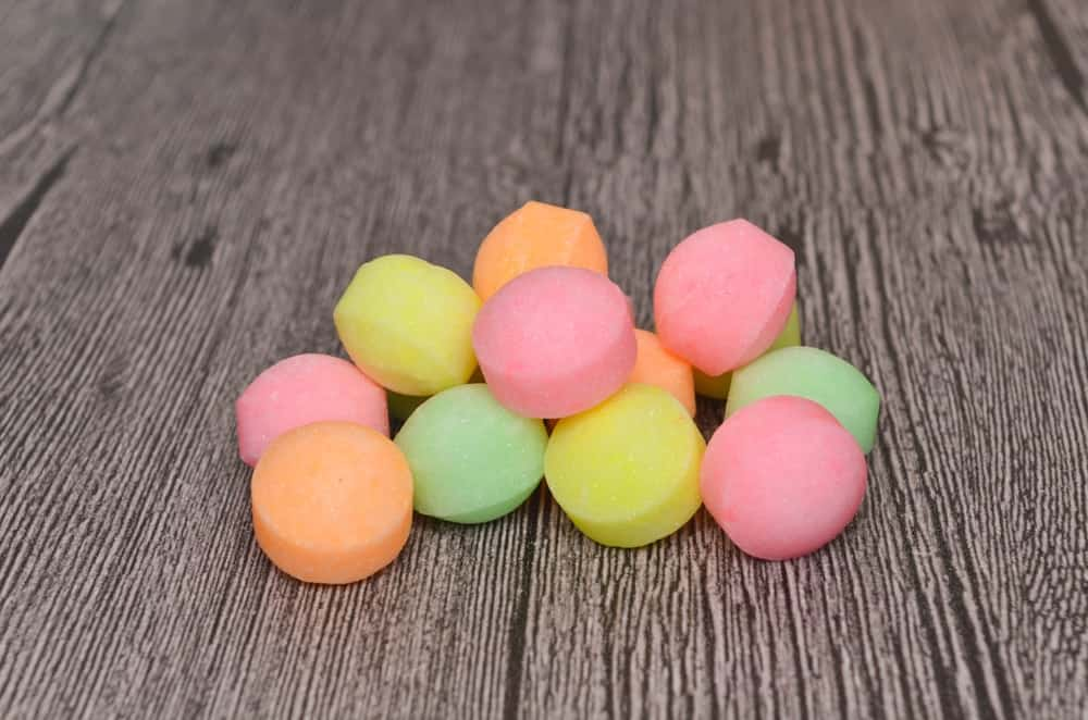 A bunch of colorful moth balls on a wooden surface.