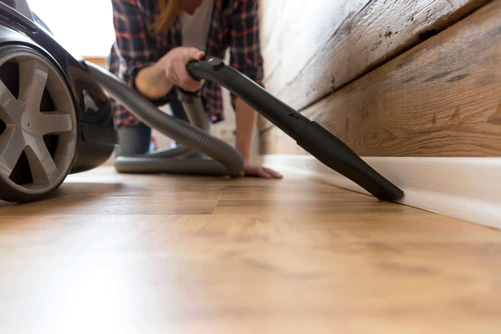 A woman vacuuming the house.