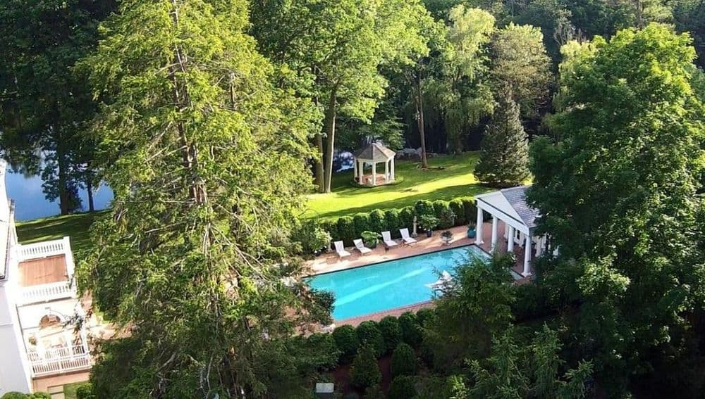 This aerial view of the backyard pool shows the light tone of the pool house that pairs well with the gazebo in the lawn of grass on the other side of the hedge wall. Images courtesy of Toptenrealestatedeals.com.