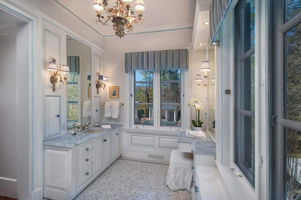 The chandelier hanging above the bathroom is a perfect match for the wall-mounted lamps flanking the vanity mirrors over the sinks. Images courtesy of Toptenrealestatedeals.com.