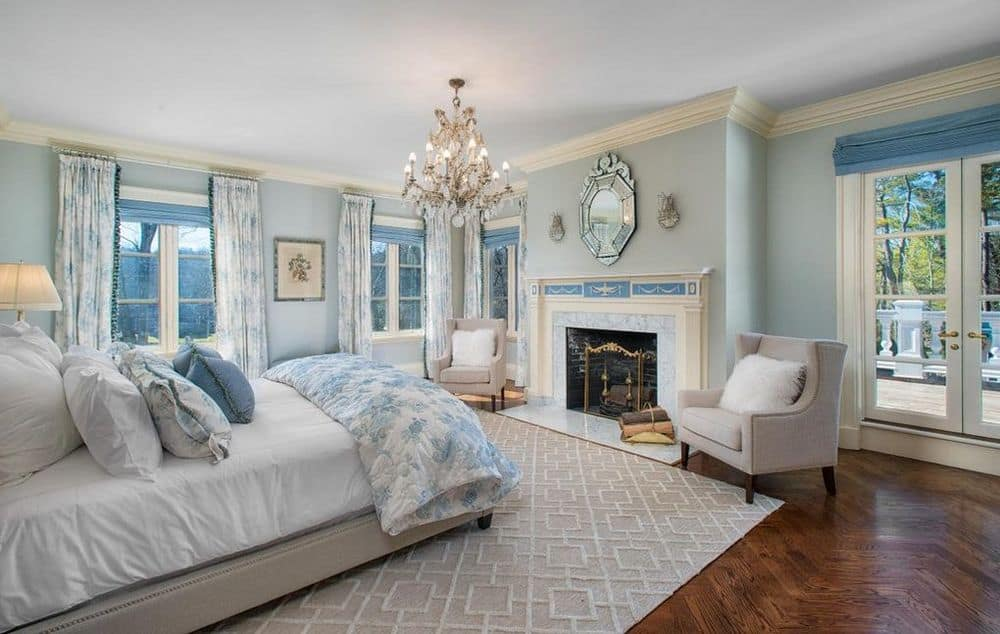 The primary bedroom has gorgeous light blue walls that complement the bright elements of the bed, fireplace mantle and crystal chandelier. Images courtesy of Toptenrealestatedeals.com.