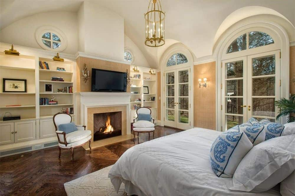 The fireplace of this bedroom is flanked by embedded book shelves and topped with a wall-mounted TV facing the bed. Images courtesy of Toptenrealestatedeals.com.