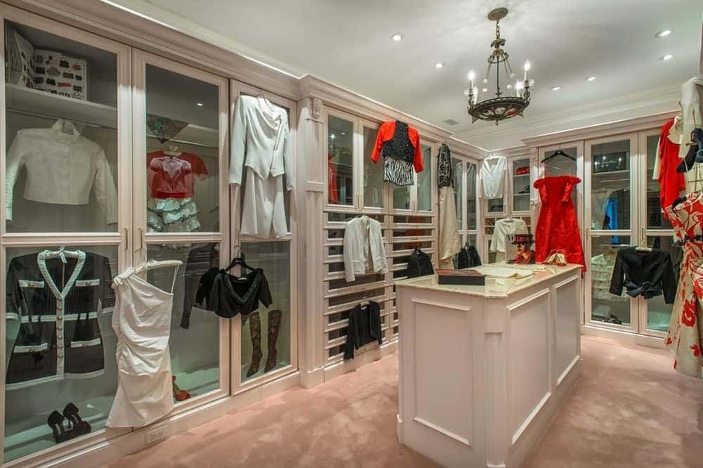 This is the walk-in closet of the house that has white wooden cabinetry and a white wooden island in the middle of the carpeted flooring. Images courtesy of Toptenrealestatedeals.com.