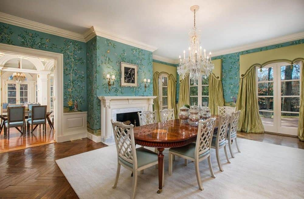 This formal dining room has gorgeous wallpaper that brings character to the walls and contrasts the white mantle of the fireplace beside the elegant dining set topped with a crystal chandelier. Images courtesy of Toptenrealestatedeals.com.