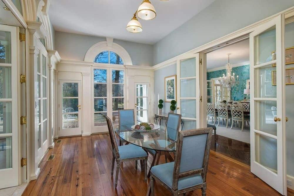 The lovely gray cushions of the dining chairs surrounding the glass dining table matches the walls and complements the hardwood flooring of the informal dining area. Images courtesy of Toptenrealestatedeals.com.