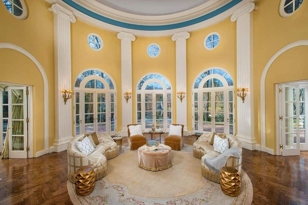 This formal living room has a tall ceiling paired with yellow walls complemented by the beige pillars to match the sofas and the round area rug. Images courtesy of Toptenrealestatedeals.com.