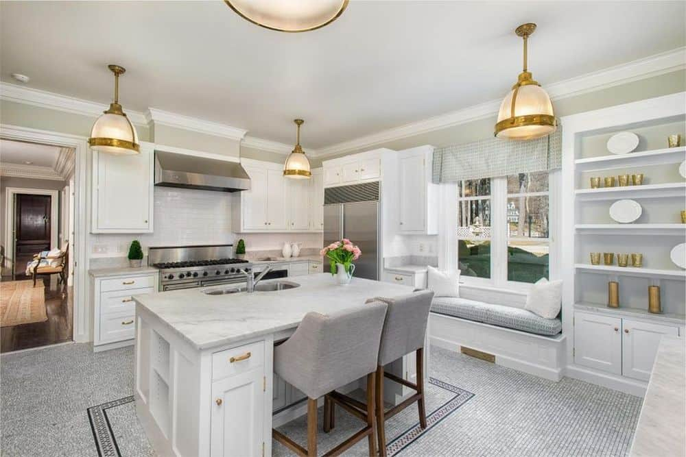 The kitchen has a white marble breakfast bar paired with a couple of cushioned stools. The kitchen island also houses the faucet area across from the cooking area. Images courtesy of Toptenrealestatedeals.com.